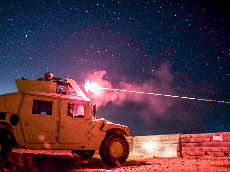 Army Military Police Service Member shoots an M240B Night-Fire Qualifications
